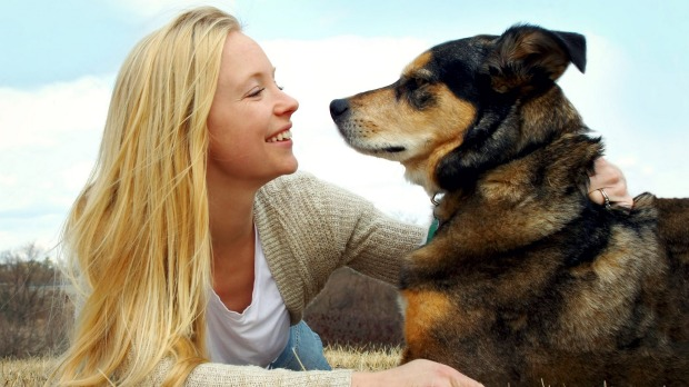 A girl and a dog looking at each other